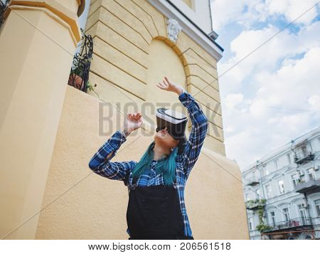 Street punk or hipster girl with blue dyed hair having fun with vr glasses. Carefree concept. Virtual reality concept. Slow motion.