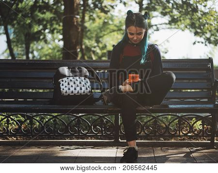 hipster girl playing tetris game in European park. Portrait of teen girl with blue dyed hair, piercing in nose, violet lenses and unusual hairstyle.Old school concept.