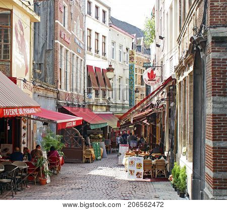 Brussels, Belgium: June 6, 2012: People are sitting and eating in street cafes in a back street in Brussels. Alfresco eating is popular across Europe.