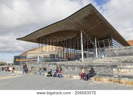 Cardiff, UK: March 10, 2016: Foreign exchange students sit on the steps of the Welsh National Assembly Building in the Cardiff Bay area. The Assembly was created by the Government of Wales Act 1998.