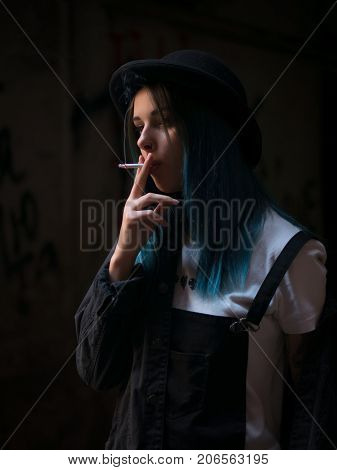 Emo girl smoking cigarette.Street punk or hipster woman with blue colorful dyed hair, hat, piercing, lenses, ears tunnels and unusual hairstyle stands in backyard. beautiful smoke.