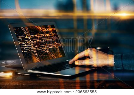 Side view of male hands at desk using laptop with abstract transport network on screen. Navigate concept. Double exposure
