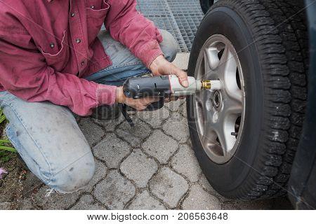 Man Unscrew Wheel Nut With An Electrical Wheel Brace