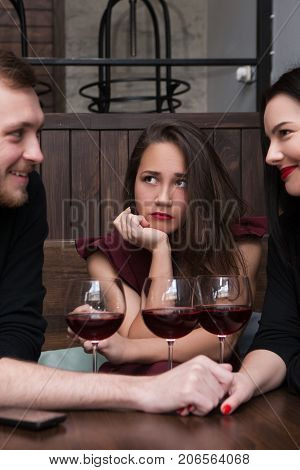 Love triangle. Female jealousy for relationship. Third wheel woman, uncomfortable situation. Cheating with friend, sad girl in romantic company, loneliness concept