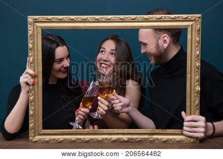 Birthday party celebration. Portrait photoshoot. Happy young company with champagne, live picture in rectangle frame. Joyful smiling people on blue background, happiness concept