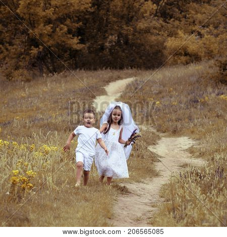 Young bride and groom playing wedding summer outdoor. Children like newlyweds. Little groom is running away from his young bride, funny kids game. Bridal, wedding concept, image toned and noise added.