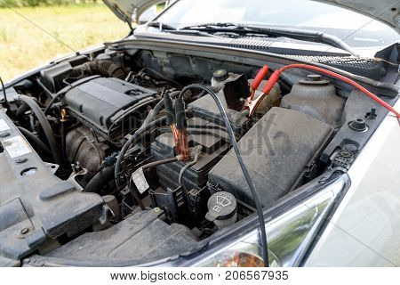 Jumper Cables Charging Battery On Car. Red And Black Car Battery Booster Cables. Charging Car Batter
