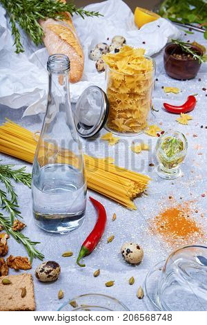 Top view of pasta, a brown jar with seasonings, wheat baguette, red hot chili peppers, little quail eggs, walnuts, a glass bottle, fusilli and different seasonings on a light gray background.