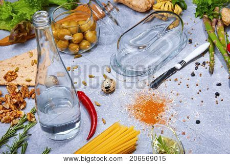Top view of yellow pasta, glass bottle with water, brown walnuts, a glass jar with olives, red hot chili pepper, green salad leaves, asparagus, a little quail egg, rosemary on a light gray background.