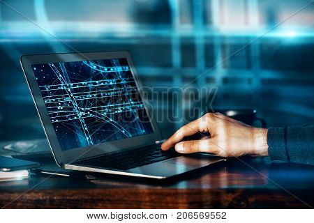 Side view of male hands at desk using laptop with abstract transport network on screen. Transportation concept. Double exposure