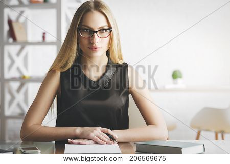 Portrait of focused young woman doing paperwork at modern office desk with items. Secretary accounting project concept