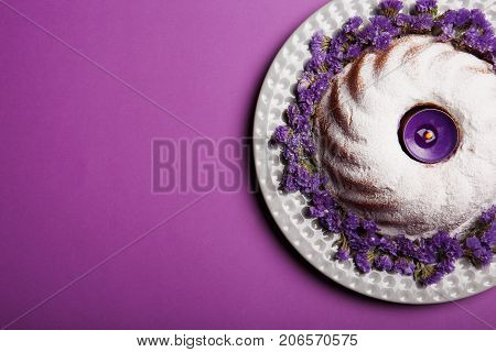 Top view of a ring cake covered with powdered sugar on a plate decorated with little purple flowers and an alight candle on a bright violet background, copy space.