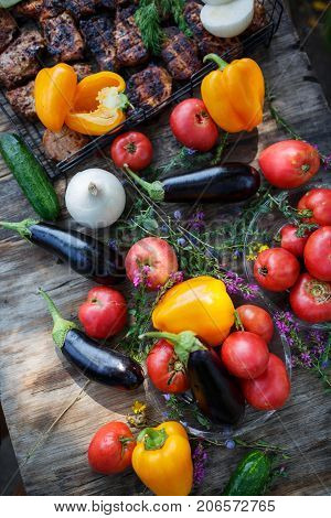 Fresh vegetables with grilled meat on a wooden table in the woods. Summer pastime in the countryside with fire and fried meat. Aptetic picnic in the summer by the river. Summer vacation in the forest.