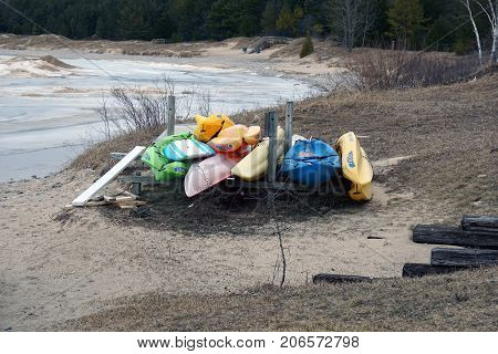 BAY VIEW, MICHIGAN / UNITED STATES - MARCH 30, 2017: Small plastic boats, belonging to residents of the Tannery Creek Condominium, are stored on their private beach for the winter season.
