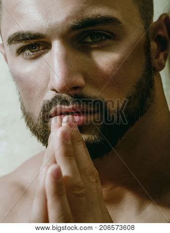 Sexy man praying and looking into camera. Portrait of handsome bearded man with beard and green eyes, masculine look and naked body. Homosexual or heterosexual male model with a beautiful face topless