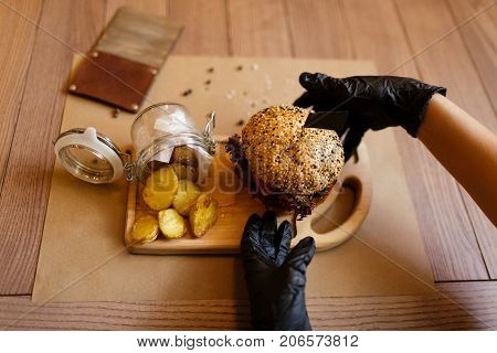 A top view of a fresh juicy meat burger and rustic potatoes on a wooden cutting desk. Fast food composition on a wooden table background, close-up. American burger. Cooking, fast food, concept.