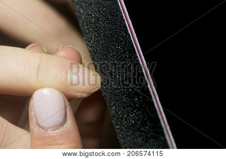 Manicure beauty salon. Nail filing. Close up, woman hands receiving a Manicure. Manicurist Filing Nails In Salon. Dry problem skin on the fingers. Tools for manicure. Dry skin in winter