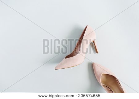 Fashion blog look. Pale pink women high heel shoes on blue background. Flat lay top view trendy beauty female background.