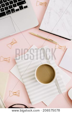Flat lay modern feminine workspace with laptop and stationery on pastel pink background. Top view.