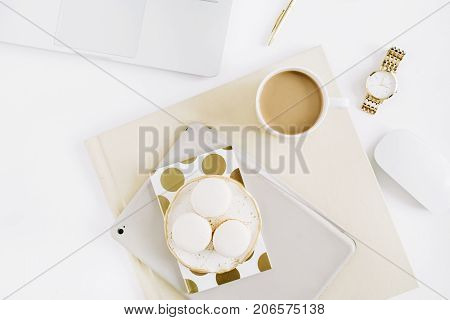 Flat lay minimal desk workspace with macaroons coffee feminine accessories. Top view modern minimal lifestyle concept.