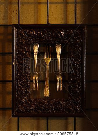 A close-up picture of three old silver forks in a metal frame on a dark wall background. Beautifully framed ancient forks for a kitchen, restaurant or cafeteria decorations.