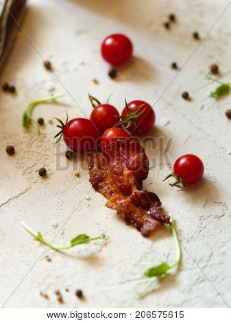 A small piece of bacon with fragrant spices and a heap of bright red cherry tomatoes on a white blurred background. Organic tomatoes, spicy peppercorns and green leaves for cooking. Delicious snacks.