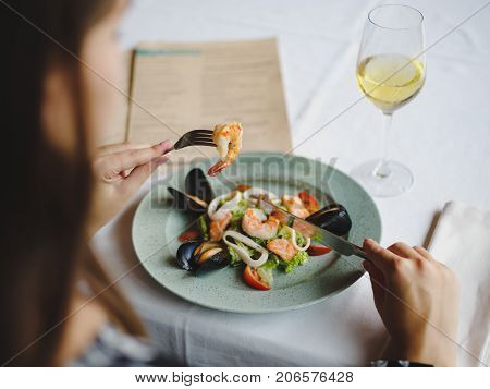 Mussels and shrimps served on a platter with a colorful fresh salad for a tasty seafood dinner. Delicious dinner at an expensive restaurant with a glass of white wine. Perfect time, healthy dinner.