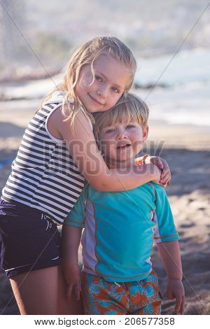 brother and sister siblings hugging outside on beach vacation