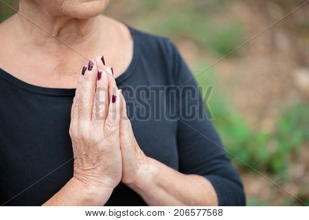 Close-up picture of a peaceful elderly woman in a black shirt, meditating in lotus position on a blurred garden background.