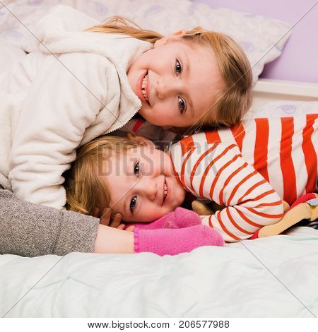 adorable brother and sister siblings cuddling together on bed