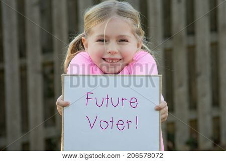 adorable school age girl wearing pink and holding sign that says future voter for women's rights