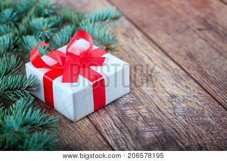 A little, white present box with a festive red bowtie next to Christmmas green pine branch on a wooden table background.
