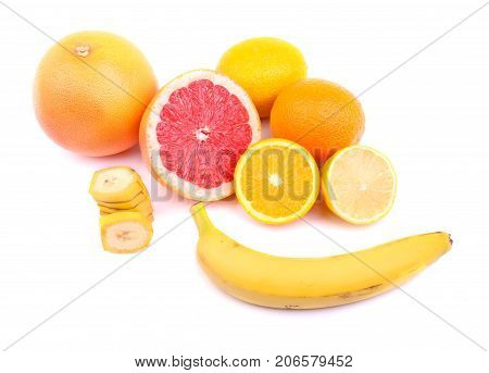 Vivid juicy lemons, grapefruit, oranges, slices of bananas and whole banana, round citruses with an acid and sweet, juicy pulp, vegetables full of vitamins for health isolated on a white background.