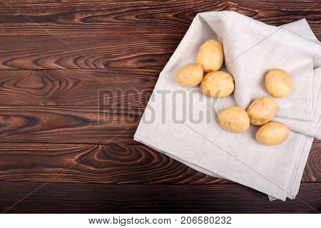 Top view of new tender potatoes on a white napkin, vegetables for healthy nutritious dishes and diets, new potatoes on a wooden table on a dark brown background. Summer harvest of young potatoes.