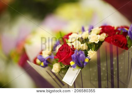 Colorful, gorgeous, amazing, blooming bouquet of flowers on a blurred flowershop background. Romantic presents at the florist shop.