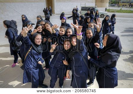 Fars Province Shiraz Iran - 19 april 2017: Merry Iranian schoolgirls show greetings gestures to the photographer's camera.