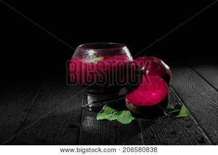 A spacious glass with refreshing, blended vegetable smoothie on a black background. Sugar cut beetroot, beetroot leaves next to dairy healthful yogurt on a black wooden table. Copy space.