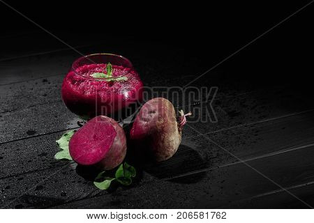 A spacious glass full of dark purple beetroot cocktail on a black table background. Nutritious beets for a healthful vegetarian salad. Vegetable juices for gourmets. Copy space. poster