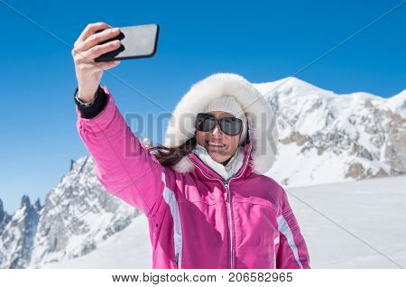 Young woman taking a selfie in winter holiday in mountain. Smiling snowboarder woman taking selfie with smartphone at ski resort. Happy woman tourist talking selfie with mountains covered with snow.