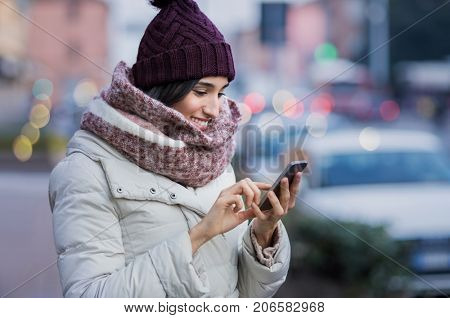 Young beautiful woman using her mobile phone at dusk in the city. Smiling girl sending message from cellphone in urban environment. Woman surfing the net with smartphone on a winter day in the street.