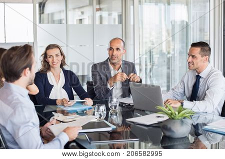Multiethnic group of business people sitting in annual meeting in conference room. Mature leader with businessmen and businesswomen discussing. Busy partners working together in modern office.