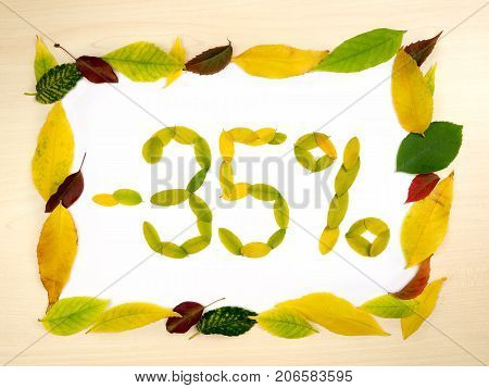 Word 35 percent made of autumn leaves inside of frame of autumn leaves on wood background. Thirty five percent sale. Autumn sale template