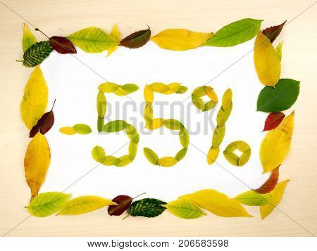 Word 55 percent made of autumn leaves inside of frame of autumn leaves on wood background. Fifty five percent sale. Autumn sale template