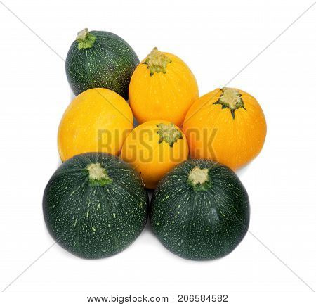 A view from above of a group of multicolored zucchini, isolated on a white background. Ripe green and yellow zucchinis for natural juices or smoothies. Vegetables for various vegetarian snacks.