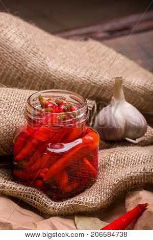 Closeup of red hot chili pepper in a glass shiny jar, white piquant garlic, rural tablecloth, ingredients for spicy disges on a light wooden background.