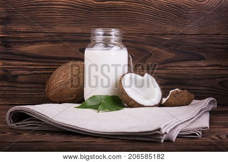 Coconut vegan milk in a mason jar with coconuts and green leaves on a gray table cloth and on a dark wooden background. Close-up of tasty and bright brown nuts. Hawaiian coconuts.