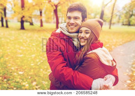 love, relationships, season and people concept - happy young couple hugging in autumn park