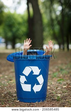 Baby's hands, sticking out from the blue bin. Playing with the trash bin, in the street, summer outdoor, save the planet, save the Earth concept. Day in park. Funny babies.