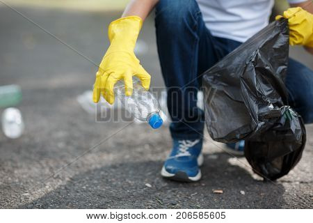 Hands in yellow gloves picking up empty of bottle plastic into bin bag on asphalt, volunteer and purity concept. Enviromental protection.