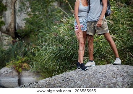 Sport legs. Woman and her man hiker climbing rock on mountain near the river. Assistance. Concept of sport and active life. Help, support, assistance in a dangerous situation